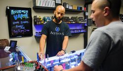 In this July 23, 2014 photo, Tyler Benjamin, left, shows a variety of batteries for e-cigarettes to Mitch Dworski on Wednesday, July 23, 2014 at Aqueous Vapor. in Columbia, Mo. Gov. Jay Nixon is eliciting support from health professionals as he tries to persuade Missouri lawmakers to sustain his veto of legislation dealing with electronic cigarettes. (AP Photo/The Columbia Daily Tribune, Nick Schnelle)