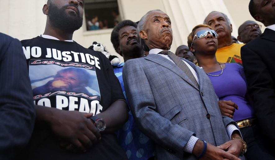 FILE - In this Aug. 12, 2014 file photo, civil rights leader Rev. Al Sharpton, center, stands with the parents of Michael Brown, Lesley McSpadden, right, and Michael Brown Sr., left, during a news conference outside the Old Courthouse in St. Louis. Lingering questions about Michael Brown could be answered Wednesday as two news organizations seek the release of any possible juvenile records for the unarmed 18-year-old who was shot by a police officer last month. (AP Photo/Jeff Roberson, File)
