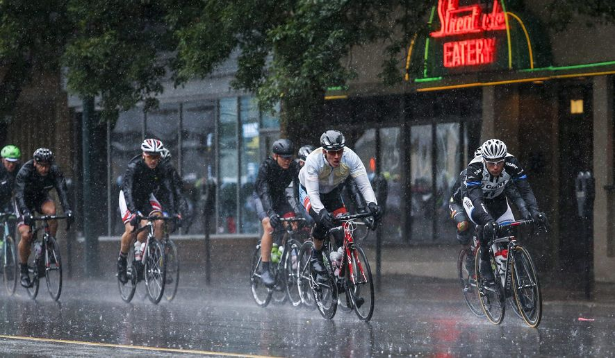 Riders pedal through downtown in heavy rain during the first stage race of the Tour of Alberta cycling race in Lethbridge, Alberta, Wednesday, Sept. 3, 2014. (AP Photo/The Canadian Press, Jeff McIntosh)