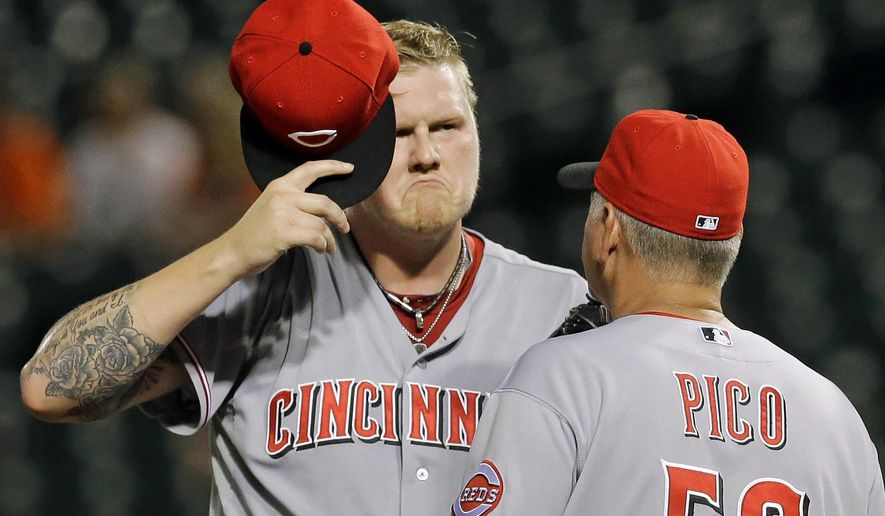 Cincinnati Reds starting pitcher Mat Latos, left, reacts as he speaks with pitching coach Jeff Pico after Baltimore Orioles' Chris Davis scored on a single by Caleb Joseph in the first inning of an interleague baseball game, Tuesday, Sept. 2, 2014, in Baltimore. (AP Photo/Patrick Semansky)