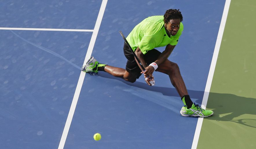 Gael Monfils, of France, returns a shot against Grigor Dimitrov, of Bulgaria, during the fourth round of the 2014 U.S. Open tennis tournament, Tuesday, Sept. 2, 2014, in New York. (AP Photo/Mike Groll)