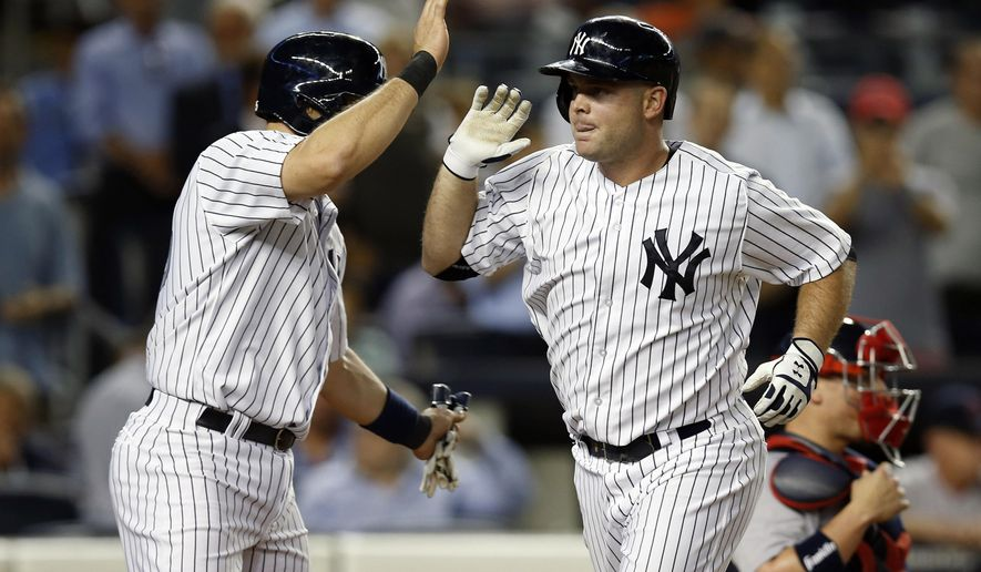 New York Yankees' Mark Teixeira, left, greets teammate Brian McCann at the plate after McCann hit a second-inning two-run home run off Boston Red Sox starting pitcher Anthony Ranaudo in a baseball game at Yankee Stadium in New York, Wednesday, Sept. 3, 2014. (AP Photo/Kathy Willens)