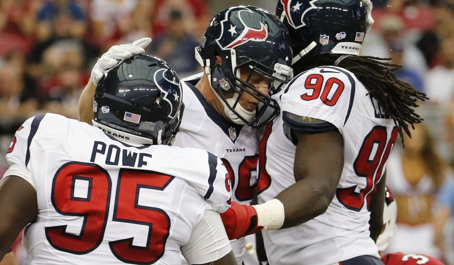 Houston Texans defensive end J.J. Watt, center, celebrates his sack with teammates Jadeveon Clowney (90) and Jerrell Powe (95) during the first half of an NFL preseason football game against the Arizona Cardinals, Saturday, Aug. 9, 2014, in Glendale, Ariz. (AP Photo/Matt York)
