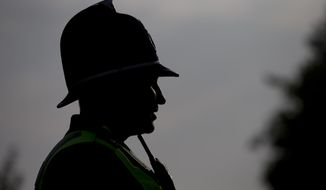 A British police officer is silhouetted as he stands guard near the Celtic Manor Resort prior to a NATO summit in Newport, Wales on Wednesday, Sept. 3, 2014. (AP Photo/Jon Super) ** FILE **