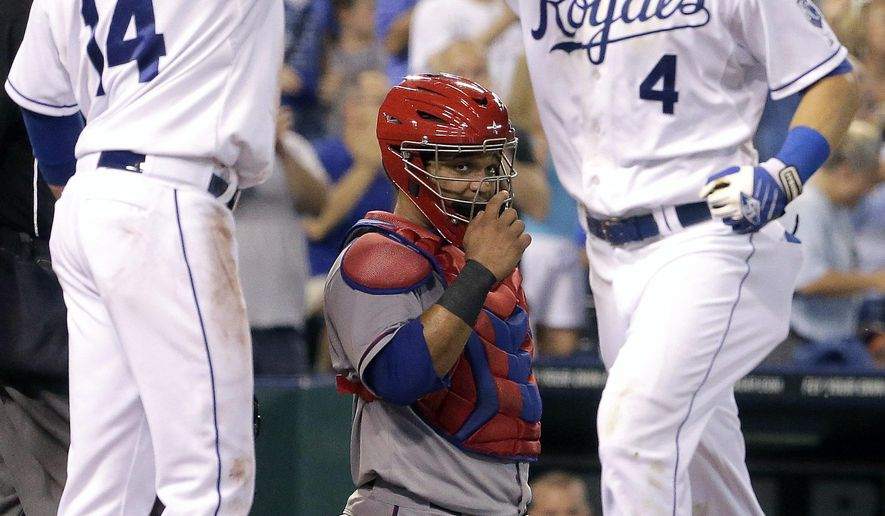 Texas Rangers catcher Tomas Telis, center, looks on as Kansas City Royals' Alex Gordon (4) celebrates with Omar Infante (14) after Gordon hit a two-run home run during the fourth inning of a baseball game Wednesday, Sept. 3, 2014, in Kansas City, Mo. (AP Photo/Charlie Riedel)