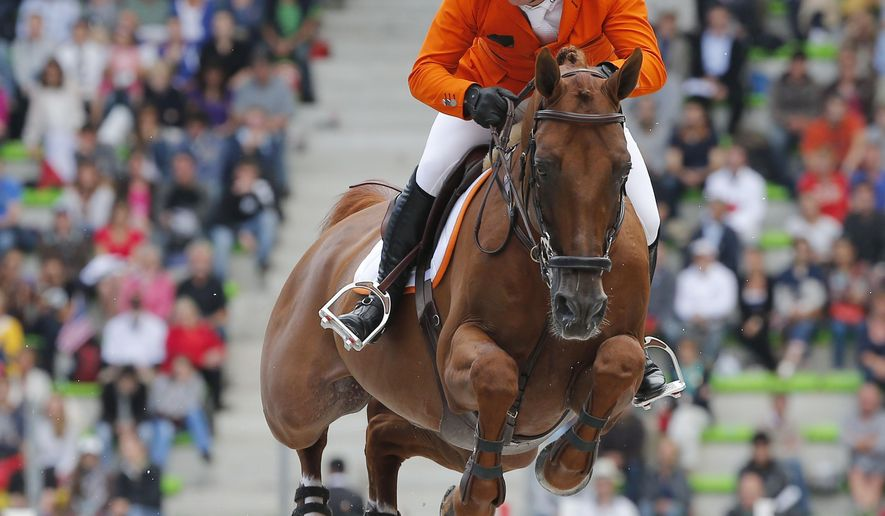 Gerco Schroeder of the Netherlands, riding Clock's London during the team and individual qualifying show jumping event at the FEI World Equestrian Games in Caen, western France, Tuesday, Sept. 2, 2014. Bertram Allen of Ireland heads in the individual in front of Patrice Delaveau of France and Gregory Wathelet of Belgium, in the team France is ahead of Sweden and the United States.  (AP Photo/Michel Euler)