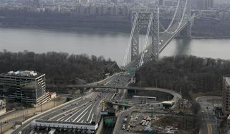 FILE - In this Dec. 1, 2013 file aerial photo, the tollbooth lanes, lower left, lead to the George Washington Bridge in Fort Lee, N.J.  According to an attorney representing their union, 11 Port Authority of New York and New Jersey police officers warned superiors about hazards created by closing some of the lanes to the George Washington Bridge in September 2013, but were advised by superiors to keep the conversation off their radios. (AP Photo/Mark Lennihan, File)