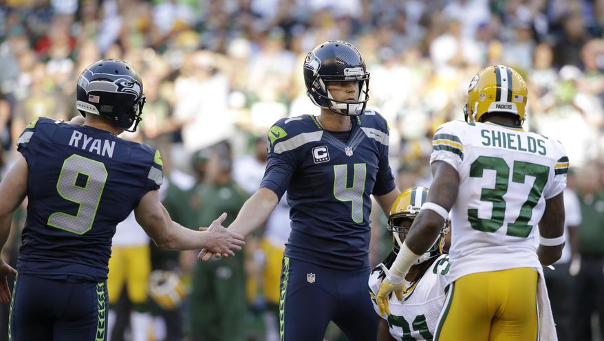 Seattle Seahawks kicker Steven Hauschka (4) slaps hands with holder Jon Ryan in front of Green Bay Packers' Sam Shields (37) after Hauschka kicked a field goal in the first half of an NFL football game, Thursday, Sept. 4, 2014, in Seattle. (AP Photo/Elaine Thompson)