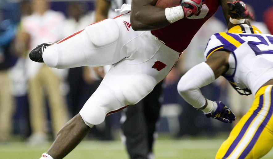 Wisconsin running back Melvin Gordon (25) leaps over LSU safety Jalen Mills (28) for a touchdown during the first half of an NCAA college football game Saturday, Aug. 30, 2014, in Houston. (AP Photo/The Courier, Jason Fochtman)