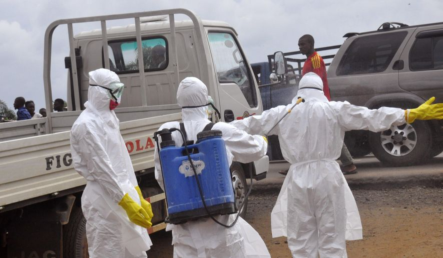 Health worker's spray each other with disinfectant chemicals as they worked with a suspected  Ebola virus death in Monrovia, Liberia, Thursday, Sept. 4, 2014. As West Africa struggles to contain the biggest ever outbreak of Ebola, some experts say an unusual but simple treatment might help: the blood of survivors. The evidence is mixed for using infection-fighting antibodies from survivors' blood for Ebola, but without any licensed drugs or vaccines for the deadly disease, some say it's worth a shot. (AP Photo/Abbas Dulleh)