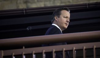 British Prime Minister David Cameron looks out from a top balcony at the Lodge as he waits for a television interview on the sidelines of a NATO summit at the Celtic Manor Resort in Newport, Wales on Thursday, Sept. 4, 2014. In a two-day summit leaders will discuss, among other issues, the situation in Ukraine and Afghanistan. (AP Photo/Virginia Mayo)