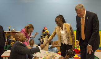 Mayor Bill de Blasio, right, visits the Inner Force Early Tots Childhood Learning Center, a community-based organization that's part of the pre-K program, as his wife Chirlane McCray shakes hands with Brooklyn borough President Eric Adams, in the Brooklyn borough of New York, Thursday Sept. 4, 2014.  City Council Speaker Melissa Mark-Viverito is second from left. It is the first day of the mayor's ambitious expansion of early childhood education. (AP Photo/The Daily News, Theodore Parisienne, Pool)