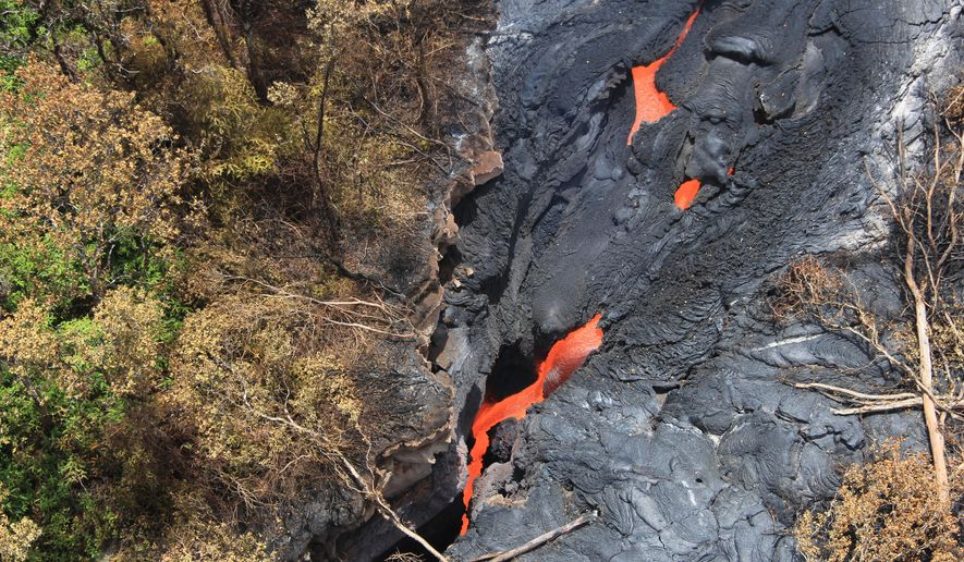 In this Sept. 1, 2014 photo released by the U.S. Geological Survey, fluid lava streams from the June 27 lava flow from the Kilauea volcano in Pahoa, Hawaii. The June 27 lava flow is named for the date it began erupting from a new vent. The Hawaiian Volcano Observatory issued a warning Thursday, Sept. 4, 2014 to a rural community in the path of a lava flow on Hawaii's Big Island, as the molten rock moved to within a mile of homes.  Observatory scientists said lava from the Kilauea volcano could reach the Kaohe Homesteads in five to seven days if it continues advancing through cracks in the earth. (AP Photo/U.S. Geological Survey)