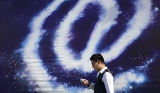 """A Chinese man checking on his smartphone walks past an """"at"""" sign on display on a street in Beijing, China Thursday, Sept. 4, 2014. The editor-in-chief and several employees of an influential Chinese financial news site were taken away by police in an investigation over allegations that the executives and journalists had extorted money from companies by threatening to publish negative news about them, the official Xinhua News Agency said Thursday. (AP Photo/Andy Wong)"""