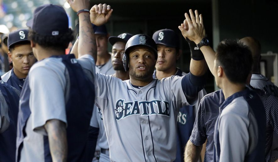 Seattle Mariners' Robinson Cano, center, is congratulated in the dugout after scoring on a Kyle Seager single in the second inning of a baseball game against the Texas Rangers, Thursday, Sept. 4, 2014, in Arlington, Texas. (AP Photo/Tony Gutierrez)