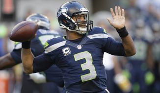 Seattle Seahawks quarterback Russell Wilson winds up to pass against the Green Bay Packers in the first half of an NFL football game, Thursday, Sept. 4, 2014, in Seattle. (AP Photo/Stephen Brashear)