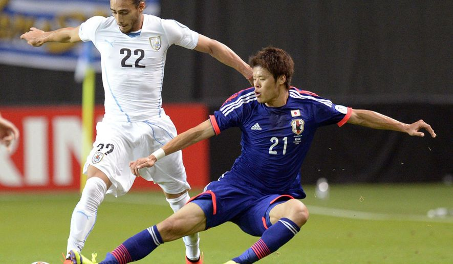Japan's Hiroki Sakai, right, and Uruguay's Martin Caceres fight for the ball during a friendly soccer match in Sapporo, northern Japan, Friday, Sept. 5, 2014. (AP Photo/Kyodo News) JAPAN OUT