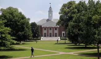 In this July 8, 2014 picture, people walk on Johns Hopkins University's Homewood campus in Baltimore. Johns Hopkins is under investigation for its handling of an alleged gang rape of a Towson University student at a fraternity house, Pi Kappa Alpha, in the spring of 2013. Since the allegation became public in May, Hopkins students have come out of the woodwork to share their own sexual assault stories, said Laura Dunn, an advocate with nonprofit organization SurvJustice who helped file the initial complaint. (AP Photo/Patrick Semansky)