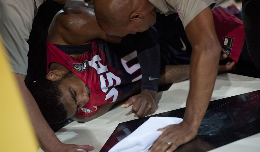Kyrie Irving of the US, is attended to on the court after falling, during the Group C Basketball World Cup match against Ukraine, in Bilbao northern Spain, Thursday, Sept. 4, 2014. The 2014 Basketball World Cup competition take place in various cities in Spain from Aug. 30 through to Sept. 14. (AP Photo/Alvaro Barrientos)