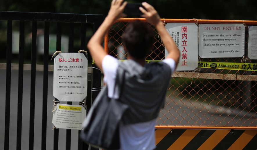 A visitor takes photos of some mosquitoes warning posters at closed gate of Yoyogi Park in Tokyo Friday, Sept. 5, 2014. Yoyogi Park, a popular park in downtown Tokyo, has been closed temporarily after dozens of cases of dengue fever were contracted by people who visited the area. (AP Photo/Eugene Hoshiko)