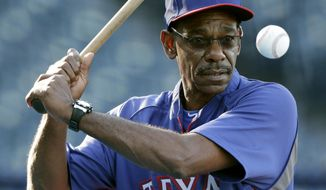 Texas Rangers manager Ron Washington hits during fielding drills before a baseball game against the Kansas City Royals, Wednesday, Sept. 3, 2014, in Kansas City, Mo. (AP Photo/Charlie Riedel)