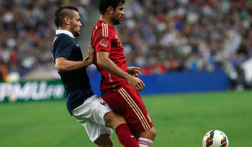 France's Mathieu Debuchy, left, vies for the ball with Spain's Diego Costa during their international friendly soccer match at the Stade de France in Saint Denis, outside Paris, Thursday, Sept. 4, 2014. (AP Photo/Thibault Camus)