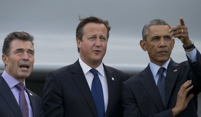 U.S. President Barack Obama, right, points as he stands alongside British Prime Minister David Cameron, center, and NATO Secretary General Anders Fogh Rasmussen during a flypast at the NATO summit at the Celtic Manor Resort in Newport, Wales on Friday, Sept. 5, 2014. (AP Photo/Jon Super) ** FILE **
