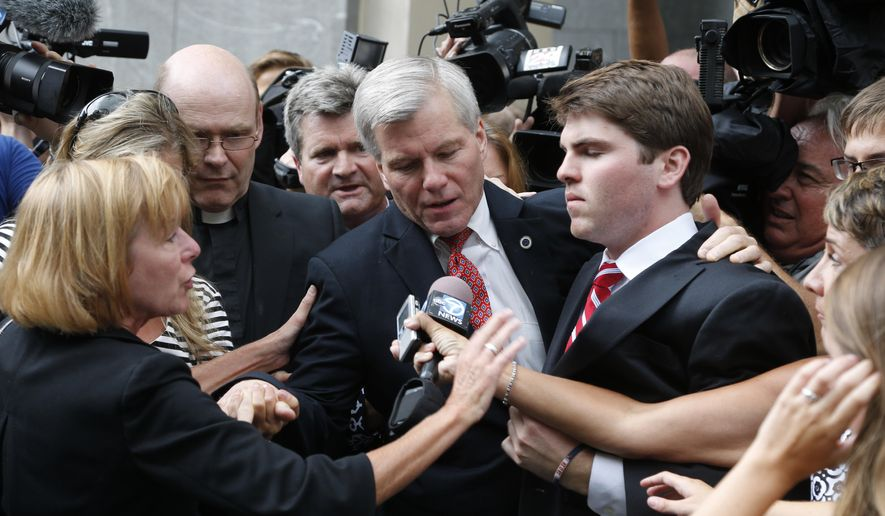 Former Virginia Gov. Bob McDonnell, center, is mobbed by media as he gets into a car with his son, Bobby, right, after he and his wife, former first lady Maureen McDonnell, were convicted on multiple counts of corruption at Federal Court in Richmond, Va., Thursday, Sept. 4, 2014. A federal jury in Richmond convicted McDonnell on 11 of the 13 counts he faced; Maureen McDonnell was convicted of nine of the 13 counts she had faced. Sentencing was scheduled for Jan. 6.  (AP Photo/Steve Helber)