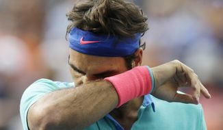 Roger Federer, of Switzerland, wipes sweat from his face between points against Marin Cilic, of Croatia, during the semifinals of the 2014 U.S. Open tennis tournament, Saturday, Sept. 6, 2014, in New York. (AP Photo/Charles Krupa)