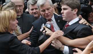 FILE - In this Sept. 4, 2014 file photo, former Virginia Gov. Bob McDonnell, center, is mobbed by media as he gets into a car with his son, Bobby, right, after he and his wife, former first lady Maureen McDonnell, were convicted on multiple counts of corruption at Federal Court in Richmond, Va. Now that the guilty verdicts on public corruption are in, attention turns to the McDonnells' Jan. 6 sentencing and subsequent appeal. (AP Photo/Steve Helber, File)