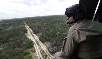 A U.S. Customs and Border Protection Air and Marine agent pears out of the open door of a helicopter during a patrol flight near the Texas-Mexico border. (AP Photo)