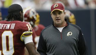 Washington Redskins head coach Jay Gruden, right, talks with Robert Griffin III during the first quarter of an NFL football game against the Houston Texans, Sunday, Sept. 7, 2014, in Houston. (AP Photo/David J. Phillip)