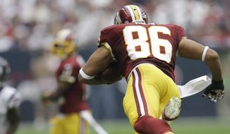 Houston Texans' Kendrick Lewis (21) trips up Washington Redskins' Jordan Reed (86) during the first quarter of an NFL football game Sunday, Sept. 7, 2014, in Houston. (AP Photo/David J. Phillip)