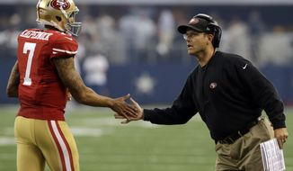 San Francisco 49ers quarterback Colin Kaepernick (7) shakes hands with head coach Jim Harbaugh after a score against the Dallas Cowboys in the first half of an NFL football game, Sunday, Sept. 7, 2014, in Arlington, Texas. (Associated Press) **FILE**