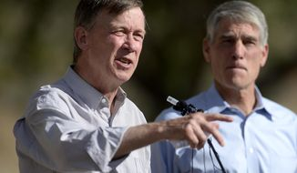 Colorado Gov. John Hickenlooper, left, speaks at news conference about progress on rebuilding the flood damaged Highway US-36 between Lyons and Estes Park as Sen. Mark Udall looks on, near Lyons, Colo., on Monday, Sept. 8, 2014. (AP Photo/Boulder Daily Camera, Mark Leffingwell)