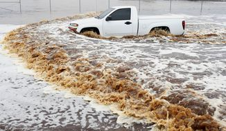 A truck creates a wake as its driver tries to navigate a severely flooded street as heavy rains pour down Monday, Sept. 8, 2014, in Phoenix. Storms that flooded several Phoenix-area freeways and numerous local streets during the Monday morning commute set an all-time record for rainfall in Phoenix in a single day. (AP Photo/Ross D. Franklin)