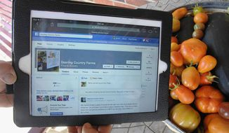 In this Aug. 12, 2014, photo, Jackie Dearing uses Facebook to promote organic vegetables and free-range poultry and beef grown at Dearing Country Farms near Bloomington, Ill. (AP Photo/The Pantagraph, David Proeber) ** FILE **