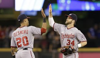 Washington Nationals' Ian Desmond (20) and Bryce Harper share congratulations after the Nationals defeated the Seattle Mariners 8-3 in a baseball game Friday, Aug. 29, 2014, in Seattle. (AP Photo/Elaine Thompson)