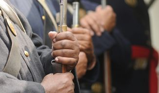 """'Living historians"""" dressed as U.S. Colored Troops hold their firearms during a recent Civil War battle re-enactment."""
