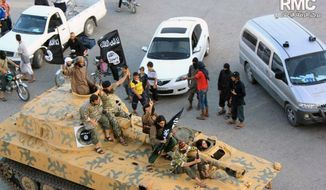 ** FILE ** In this undated file image posted by the Raqqa Media Center, a Syrian opposition group, on Monday, June 30, 2014, which has been verified and is consistent with other AP reporting, fighters from Islamic State group sit on their tank during a parade in Raqqa, Syria. (AP Photo/Raqqa Media Center, File)