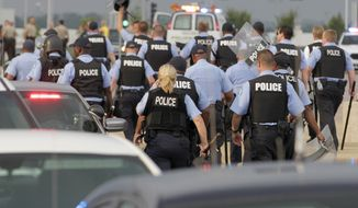 St. Louis city police stand down after an attempt to shut down interstate 70 was stifled, Wednesday, Sept. 10, 2014 in Berkeley, Mo. near the St. Louis suburb of Ferguson, Mo. where Michael Brown, an unarmed, black 18-year old was shot and killed by a white police officer on Aug. 9. (AP Photo/Tom Gannam)
