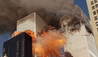 In this Sept. 11, 2001, file photo, smoke billows from World Trade Center Tower 1 and flames explode from Tower 2 as it is struck by American Airlines Flight 175, in New York. (AP Photo/Chao Soi Cheong, File)