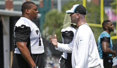 Jacksonville Jaguars head coach Gus Bradley, right, talks with Red Bryant during an NFL football minicamp in Jacksonville, Fla., Tuesday, June 17, 2014. (AP Photo/John Raoux)