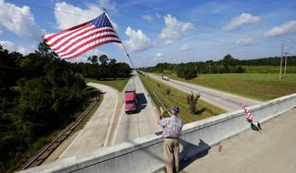 Ben Kinsey waves a flag from an I-20 overpass, Thursday, Sept. 11, 2014, in North Augusta, South Carolina. Kinsey is a 14-year veteran of the USMC, USArmy and Georgia National Guard who felt compelled to stand in the heat and wave his flag after attending a 9/11 ceremony last year. This is the second year he has paid tribute to the first responders that gave their lives on 9/11/01 and wants to remind everyone of their sacrifices. He said it's easy tell when a veteran drives by, they give the flag a fast salute as they speed by. (AP Photo/The Augusta Chronicle, Todd Bennett)