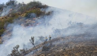 Firefighters work on a brush fire in Silverado Canyon in Orange County, Calif. on Friday, Sept. 12, 2014. (AP Photo/Orange County Register, Sam Gangwer)
