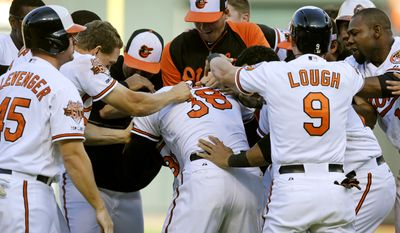 Members of the Baltimore Orioles celebrate with Jimmy Paredes (38) after he batted in two runs in the 11th inning in the first baseball game of a doubleheader against the New York Yankees, Friday, Sept. 12, 2014, in Baltimore. Baltimore won 2-1. (AP Photo/Patrick Semansky)