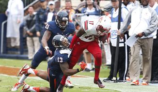 Louisville wide receiver James Quick (17) tries to break the tackle of Virginia linebacker Daquan Romero (13) and safety Brandon Phelps (21) during the first half of an NCAA college football game in Charlottesville, Va., Saturday, Sept. 13, 2014. (AP Photo/Steve Helber)