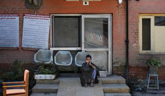A Kashmiri man sits in the compound of a hospital which resumed its services after the floods hit Srinagar, India, Saturday, Sept. 13, 2014. About 200 people have died in Indian-controlled Kashmir, where floodwaters have receded, enabling people to return to their homes. Medical teams in Srinagar, the main city in Indian-held Kashmir, were stepping up efforts to prevent the spread of waterborne diseases, officials said Saturday. (AP Photo/Altaf Qadri)