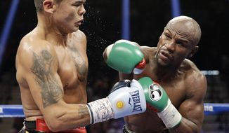 Floyd Mayweather, right, follows through on a punch at Marcos Maidana during their title boxing match Saturday, Sept. 13, 2014, in Las Vegas. (AP Photo/John Locher)