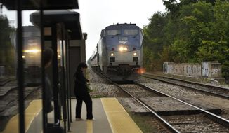 In a Friday, Sept. 12, 2014 photo, an Amtrak train bound for Chicago approaches the Royal Oak Station in Royal Oak, Mich. as passengers wait to board. The Michigan Senate has cleared the way for the state to upgrade the speed and comfort of Amtrak services between Detroit and Chicago. Transportation officials plan to buy two sets of cars and engines to allow trains to reach 110 mph and cut transit time by up to two hours in coming years. (AP Photo/Detroit News, John T. Greilick)  DETROIT FREE PRESS OUT; HUFFINGTON POST OUT